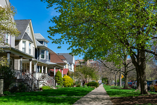A row of old wooden homes with front lawns and a sidewalk in the North Center neighborhood of Chicago