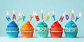 istock Row of orange and blue birthday cupcakes 1308886360