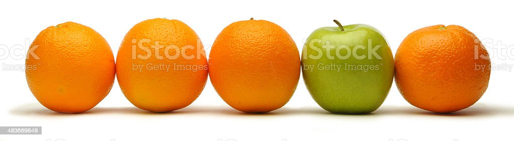 Row of oranges with a green apple. stock photo