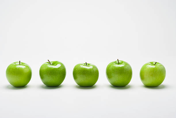 Row of Organic Granny Smith apples A row of five organic green Granny Smith  apples with position appropriate reflections and shadows  on white background granny smith apple stock pictures, royalty-free photos & images