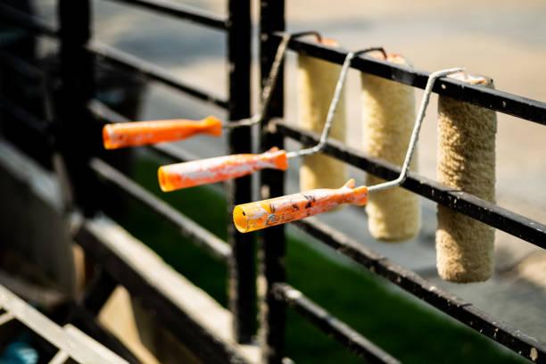 rangée de couvercle de rouleau de peinture accroché sur un rail noir. - rame pièce détachée photos et images de collection