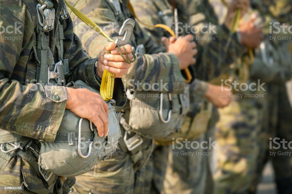 row of paratrooper in camouflage uniform hold T-10 static line hook and parachute reserve in cinematic tone stock photo