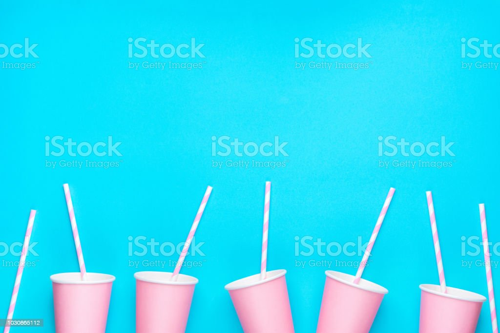 Row of pink empty paper cups striped drinking straws arranged in bottom border on mint blue background. Creative flat lay. Birthday party celebration kids baby shower. Pastel Colors. Poster banner stock photo