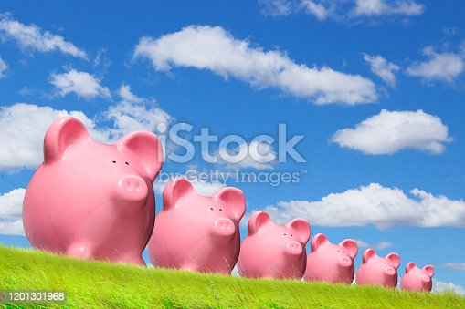 A row of pink piggy banks in a field of grass under a blue sky punctuated with clouds.