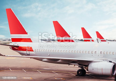 Row of plane fuselage tails on tarmac at airport