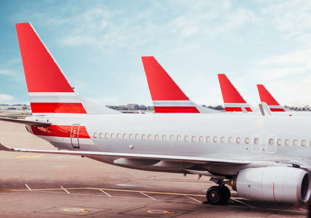 Row of plane fuselage tails on tarmac at airport stock photo