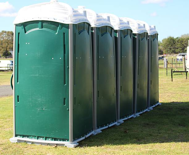 Row of portable toilets Row of portable toilets available to the public at a summer event portable toilet stock pictures, royalty-free photos & images