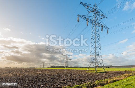 istock Row of power pylons at the edge of a plowed field 858970742