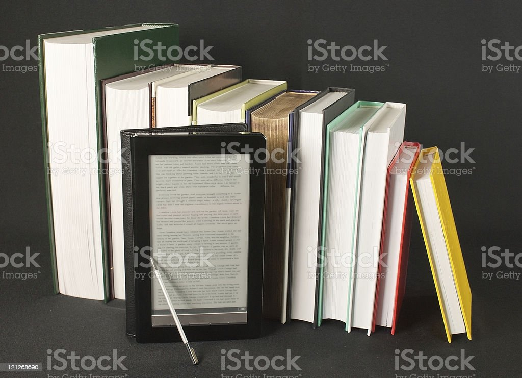Row of printed books with electronic book reader on black royalty-free stock photo