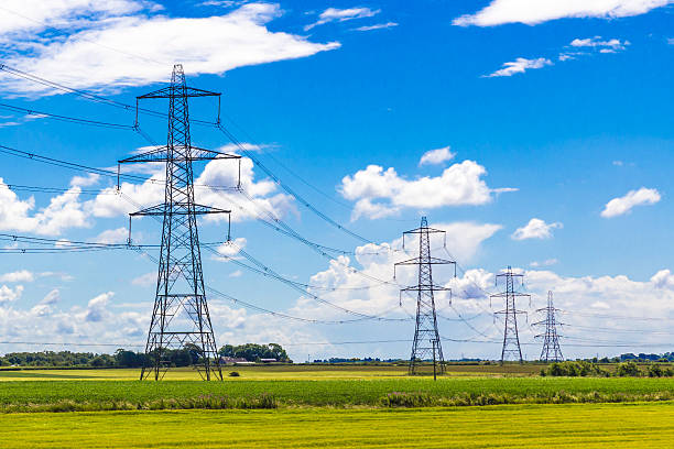 row of pylons - hoogspanningsmast stockfoto's en -beelden