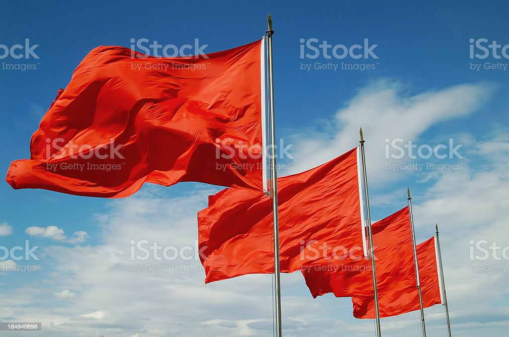 A row of red flags blowing in the wind stock photo