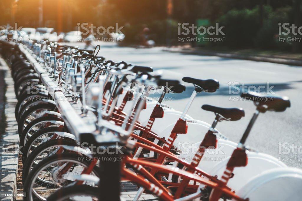 Fila de bicicletas de alquiler de color rojo al aire libre - Foto de stock de Aire libre libre de derechos