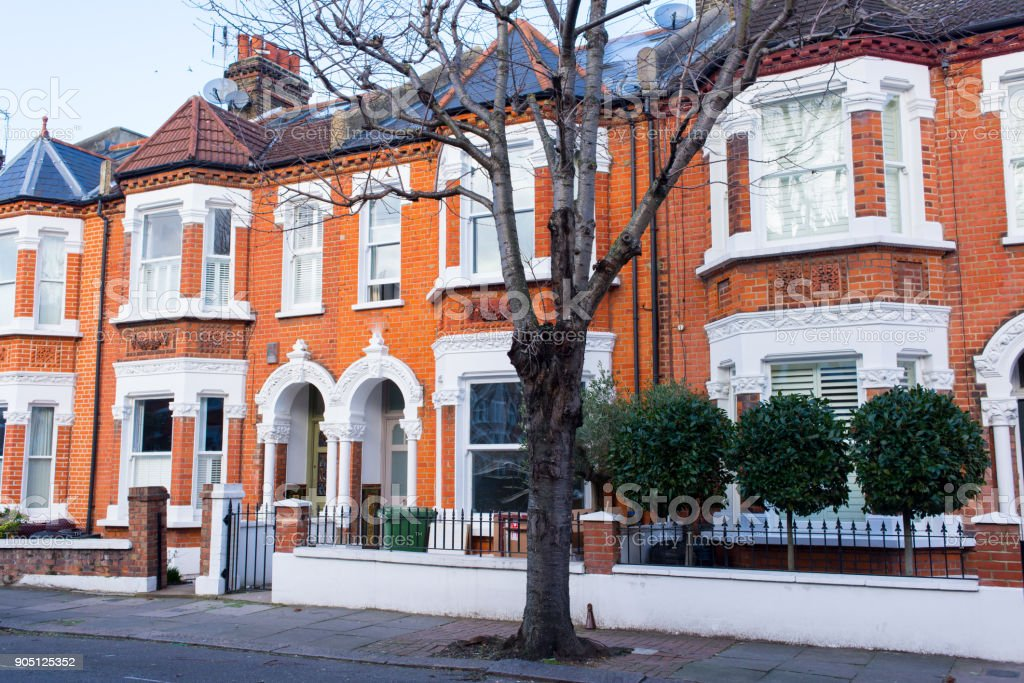 Row of restored Victorian house in red bricks and white finishing on a local street in Clapham, South London, UK stock photo