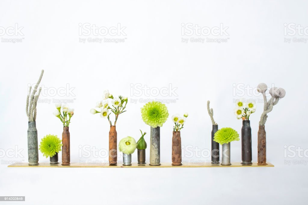 Row of Rusty Bullet Casings or Shells Hold Flowers and Plants stock photo