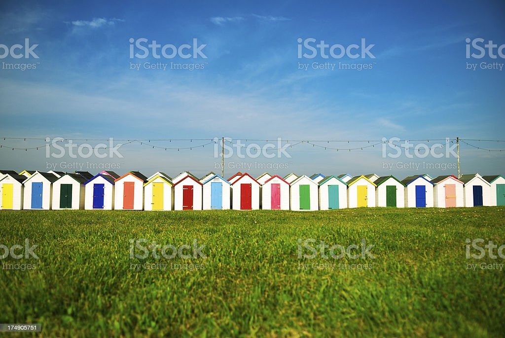 Row of Seaside Huts with Colorful Doors Above Grass stock photo