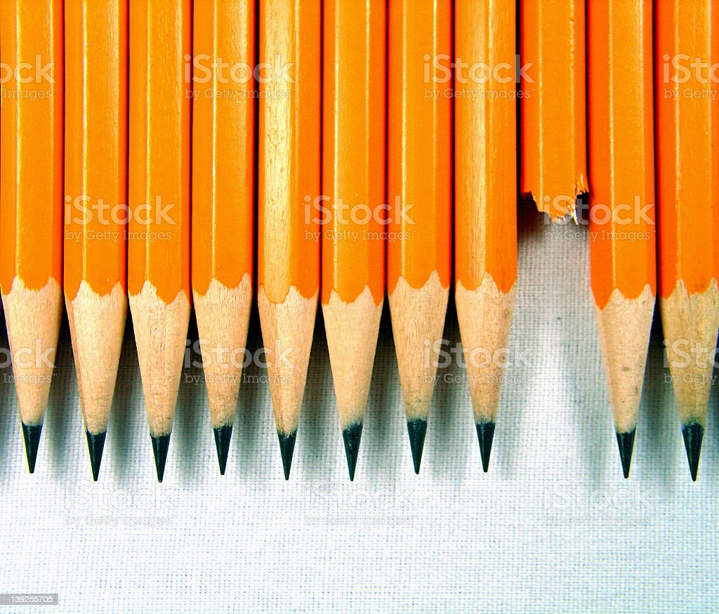 A row of sharpened pencils with one broken stock photo