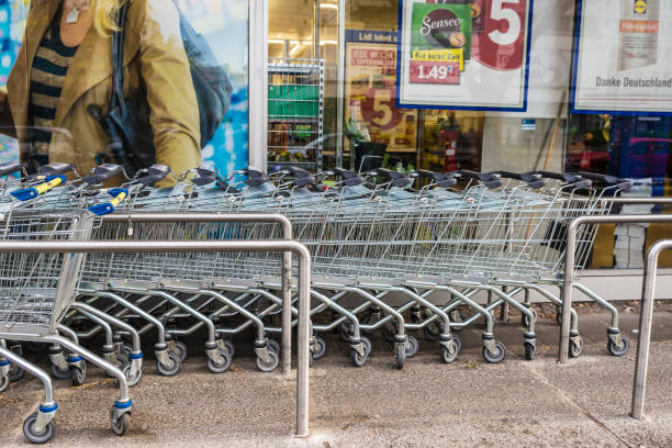 row of shopping carts in front of a lidl supermarket - lidl foto e immagini stock
