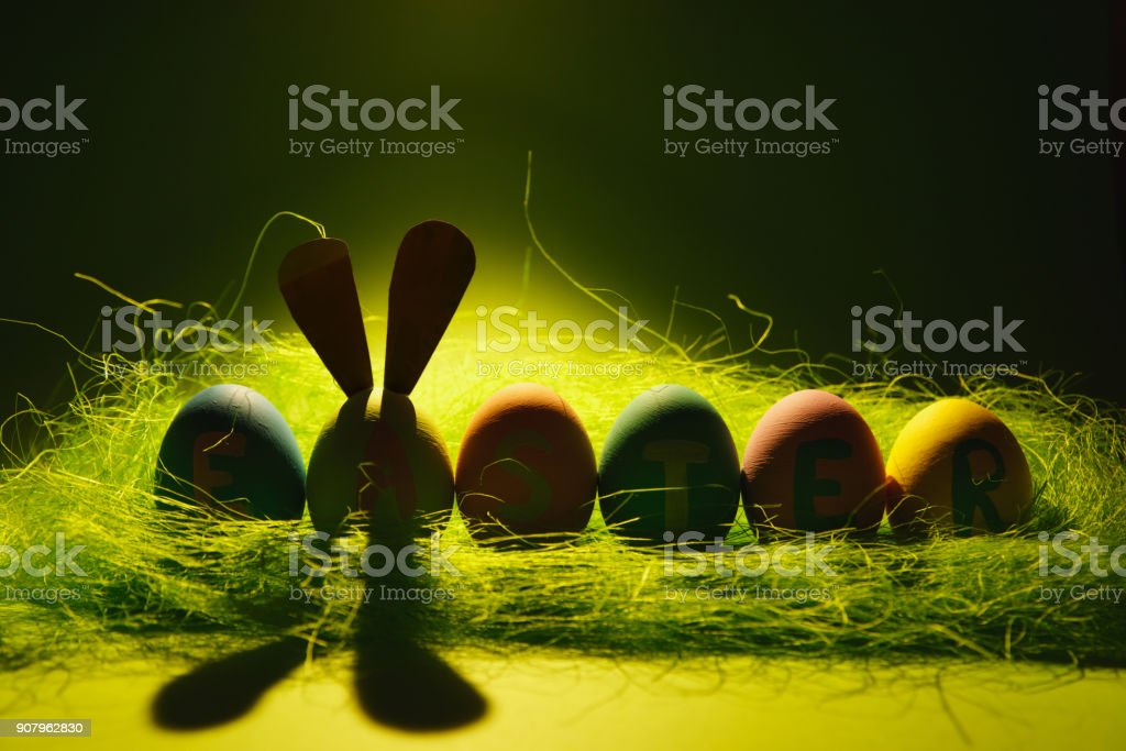 Row of six colorful pastel monophonic painted Easter eggs with inscription Easter, fun bunny ears on egg in green grass isolated on dark green background with shadows and light. For advertisement. stock photo