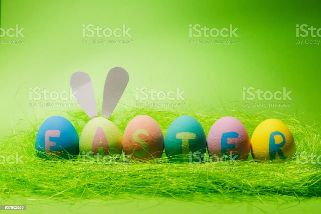 Row of six colorful pastel monophonic painted Easter eggs with inscription Easter, fun bunny ears on egg in green grass isolated on green background. Copy space for advertisement. With place for text stock photo