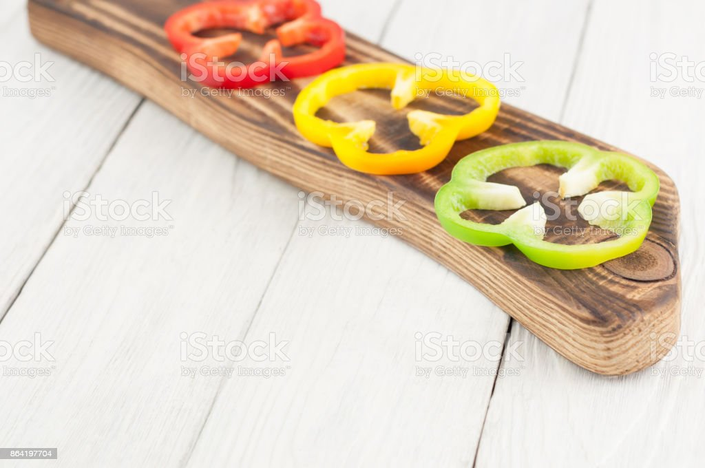 Row of slices of colored red and yellow and green fresh ripe raw pepper on brown cutting board on old rural white wooden planks royalty-free stock photo
