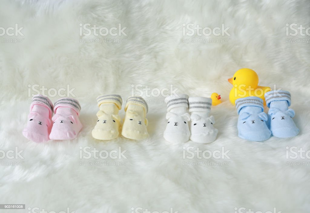 Row of Socks for newborn babies on the white fur background with decoration rubber ducks. stock photo