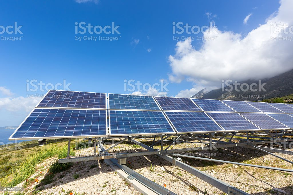 Row of solar collectors on mountain with blue sky stock photo