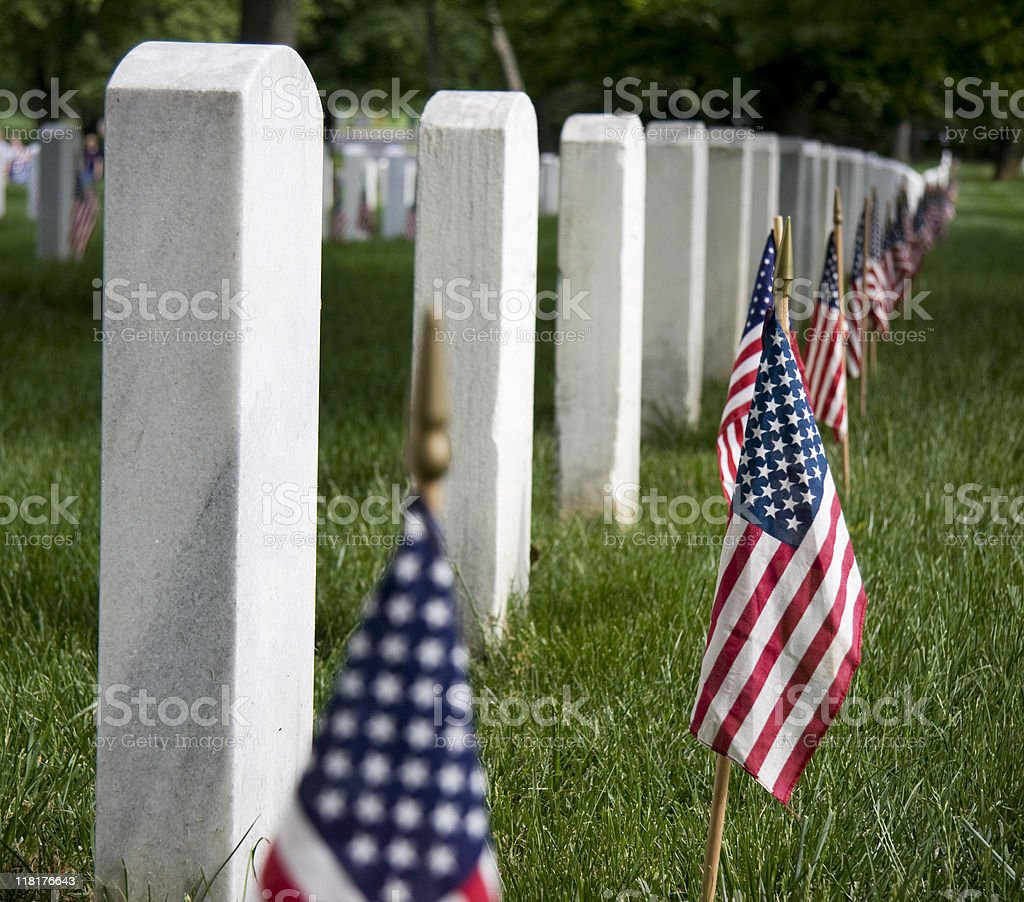 Row of soldiers headstones with American flags stock photo