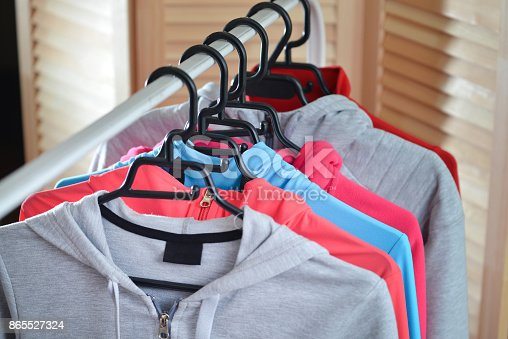 istock Row of sport shirts and jackets hanging on clothes rack at a fashion store 865527324