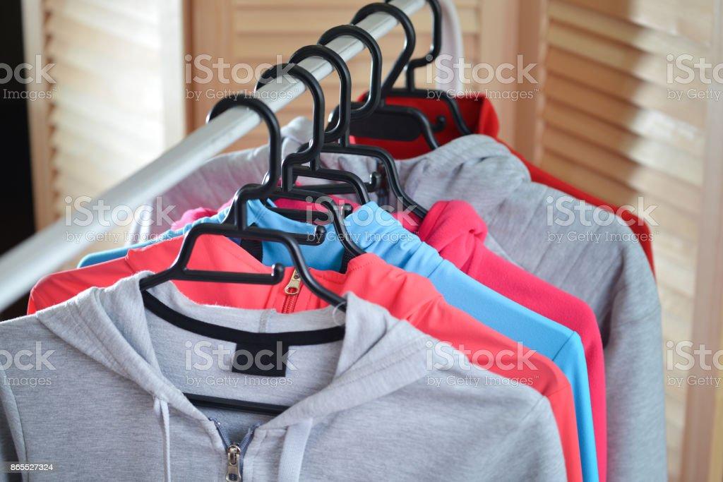 Fila de camisas deportivas y chaquetas colgadas en estante de la ropa en una tienda de moda - foto de stock