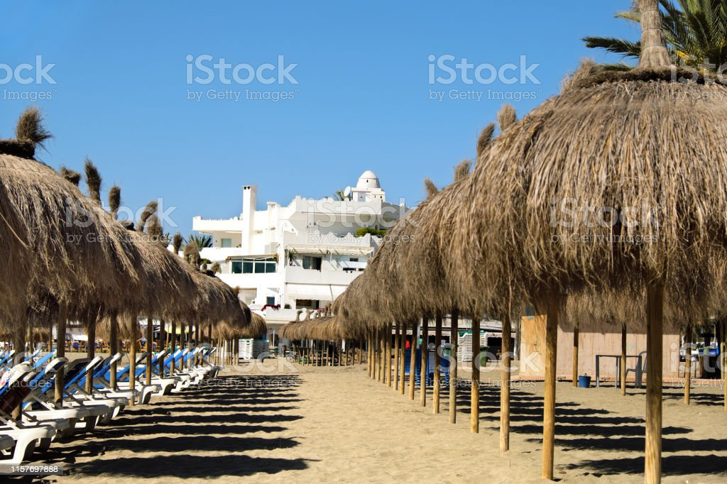 Row Of Straw Umbrellas With Sunbeds On The Beach In Marbella