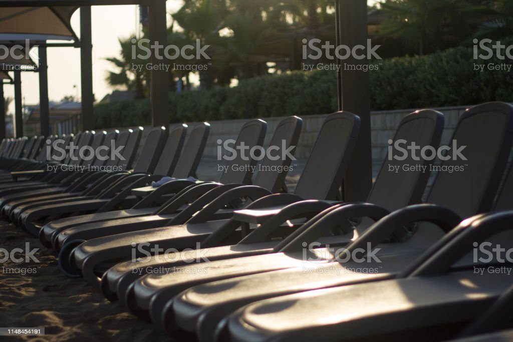 Row Of Sunbeds With Umbrellas On The Beach By The Sea At