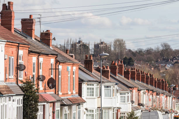 Row of terraced house roofs with chimney stacks stock photo
