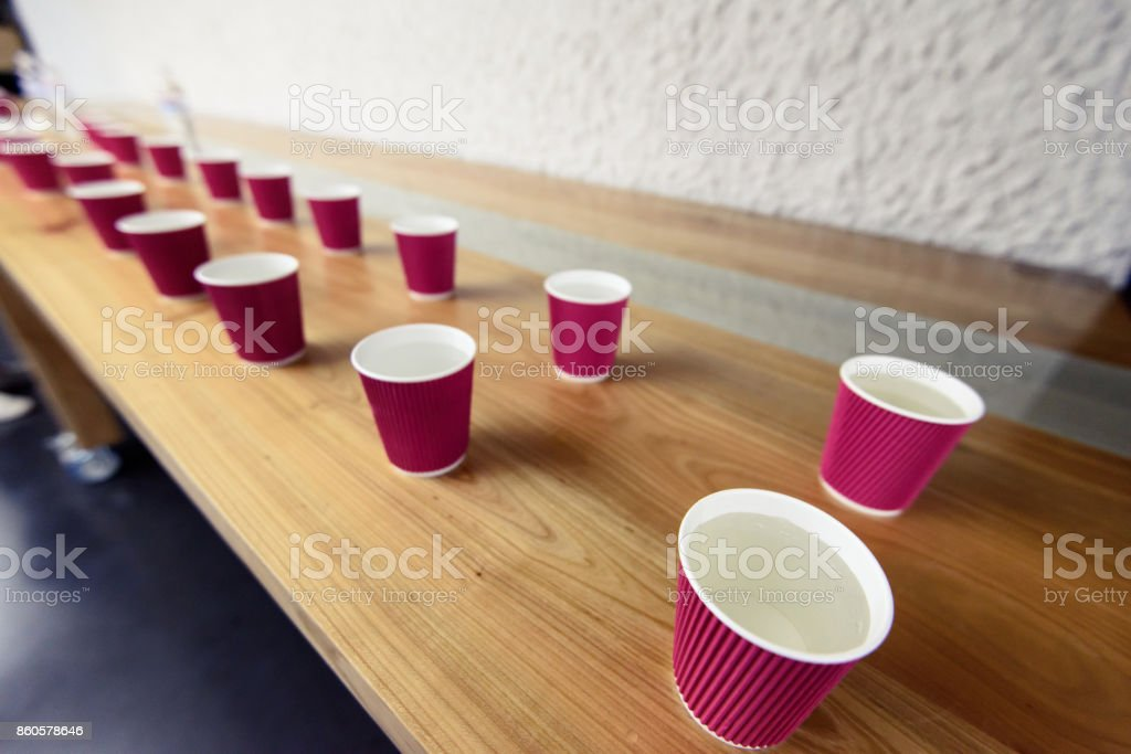 A row of the disposable paper cups with water on the wooden table....