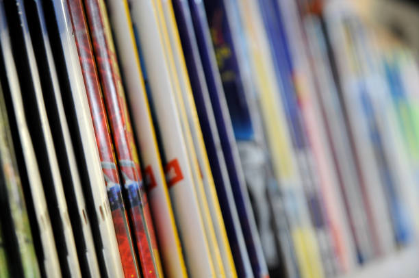 A row of thin, staple-bound magazines in a kiosk focus on the white and red magazines on the left. SEE HERE RELATED IMAGES: news stand stock pictures, royalty-free photos & images