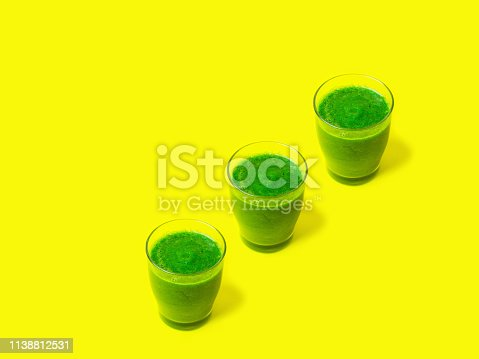 istock Row of three glasses of leafy greens smoothies spinach vegetables fruits on bright sunny yellow background. Healthy plant based diet detox vegan concept. Creative food poster 1138812531