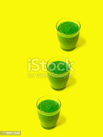 istock Row of three glasses of leafy greens smoothies spinach vegetables fruits on bright sunny yellow background. Healthy plant based diet detox vegan concept. Creative food poster. Vertical 1138812535