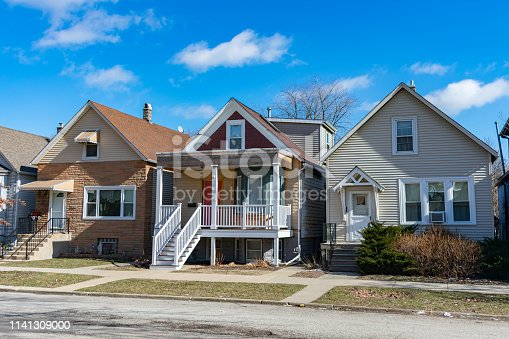 A row of three simple wooden homes in the Chicago neighborhood of Logan Square