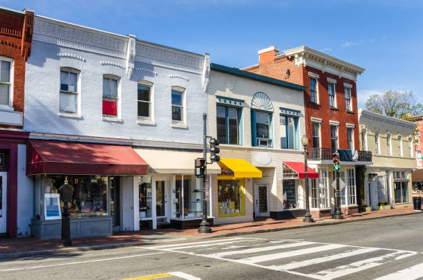 row of traditional american brick buildings with colourful shops under blue sky - via principale foto e immagini stock