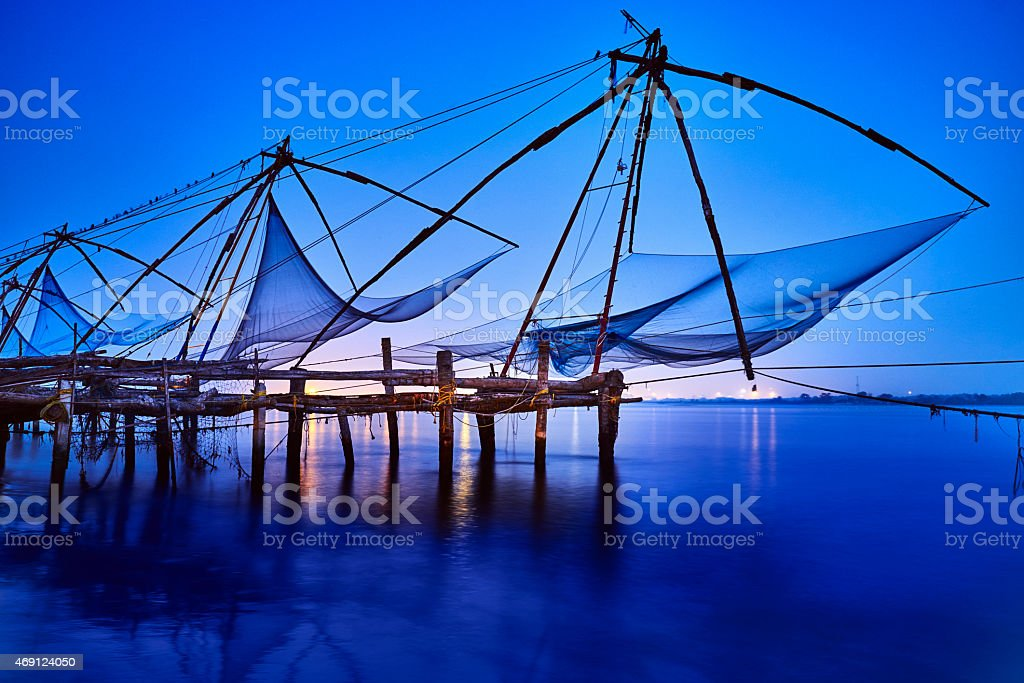 Row of traditional indian fishing nets in blue sunset mood stock photo