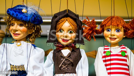 Row of traditional puppets - charming prince, young peasant and carefree girl