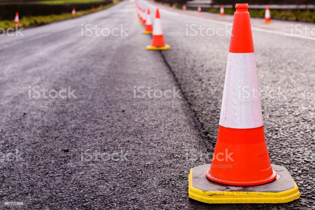 Zeile der Leitkegel entlang der Mitte einer Straße wird neu asphaltiert. – Foto