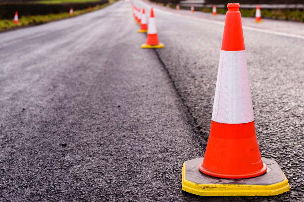 Row of traffic cones along the middle of a road being resurfaced. Row of traffic cones along the middle of a road being resurfaced. boundary stock pictures, royalty-free photos & images