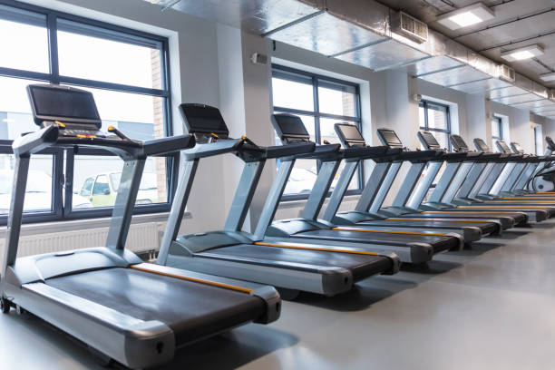 Row of treadmills in a gym Gym interior with treadmills in a row. Exercising machines in modern health club. training equipment stock pictures, royalty-free photos & images