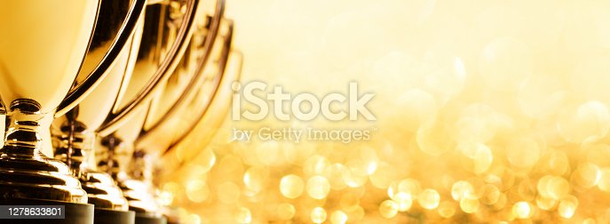 A row of trophies cropped in a panoramic photographed with a very shallow depth of field on a background of glitter and blurred lights.