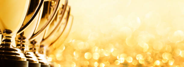 Row Of Trophies On Golden Background stock photo