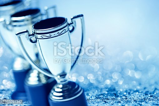A group of trophies photographed with a very shallow depth of field as glitter and confetti abound in the background. A cool blue cast dominates the scene.