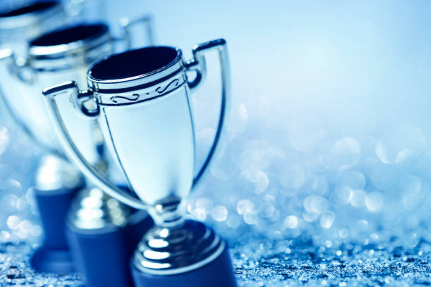 Row Of Trophies With Glitter And Confetti A group of trophies photographed with a very shallow depth of field as glitter and confetti abound in the background. A cool blue cast dominates the scene. trophy award stock pictures, royalty-free photos & images