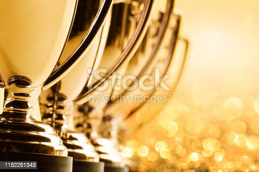 A group of trophies photographed with a very shallow depth of field as glitter and confetti abound in the background. A warm golden cast dominates the scene.
