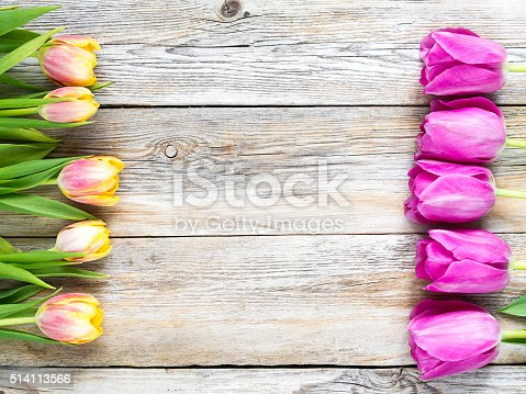 921112244 istock photo Row of tulips on wooden background with space for message. 514113566