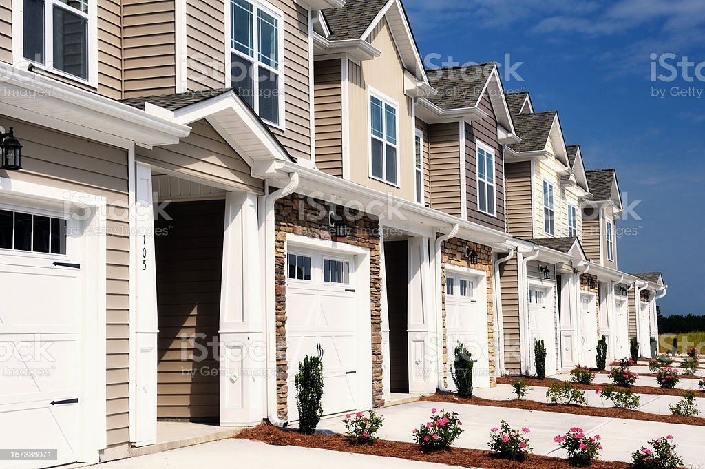 Row of two-story houses with white garages stock photo